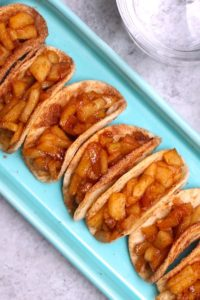Super Easy Fried Apples with Homemade Tacos – delicious cinnamon sugary fried apples in a crispy and sweet taco, drizzled with caramel sauce, and then topped with whipped cream! The easiest dessert that comes together in no time. All you need is a few simple ingredients: Flour Tortillas, butter, cinnamon, sugar, apples, lemon, caramel sauce and whipped cream. It's the perfect way to serve apple pie to a crowd!