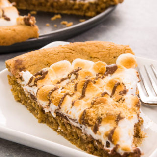S'mores Pie / S'more Pizza is gooey, chocolatey, rich and crunchy making a perfect crowd-pleaser. It's such an easy recipe that takes less than 30 minutes. Who needs a campfire? The combination of graham cracker crust, toasted marshmallow and rich chocolate come together, in the form of a delicious pie. So good! Quick and easy recipe. | Tipbuzz.com #smoresPie #smoresPizza