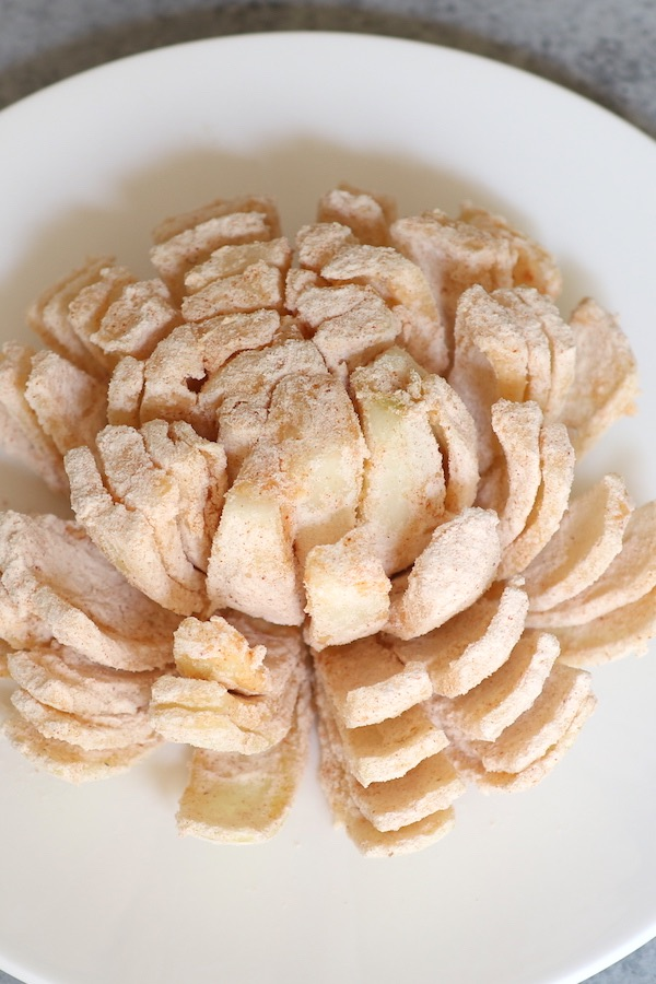 An onion cut to an onion flower, seasoned and battered. It's placed on a white plate and ready to be deep fried.