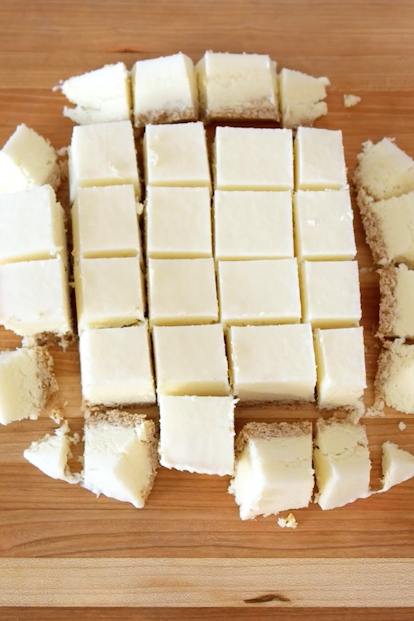 Frozen cheesecake is cut into many 1-inch pieces  on a wooden cutting board