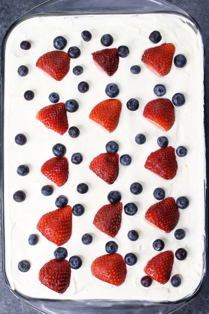 Layers of pudding mixture, graham crackers and strawberries are assembled in a clear 13x9 inch dish on the counter
