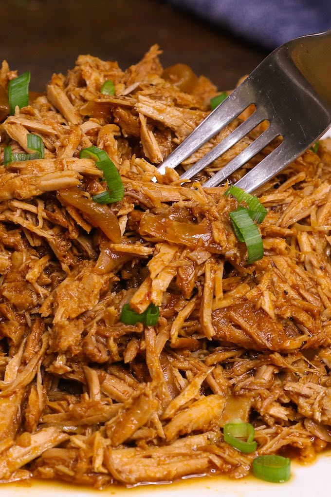 Shredded crock pot pork shoulder served on a white plate