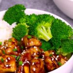 teriyaki chicken served on top of rice with steamed broccoli in a white bowl