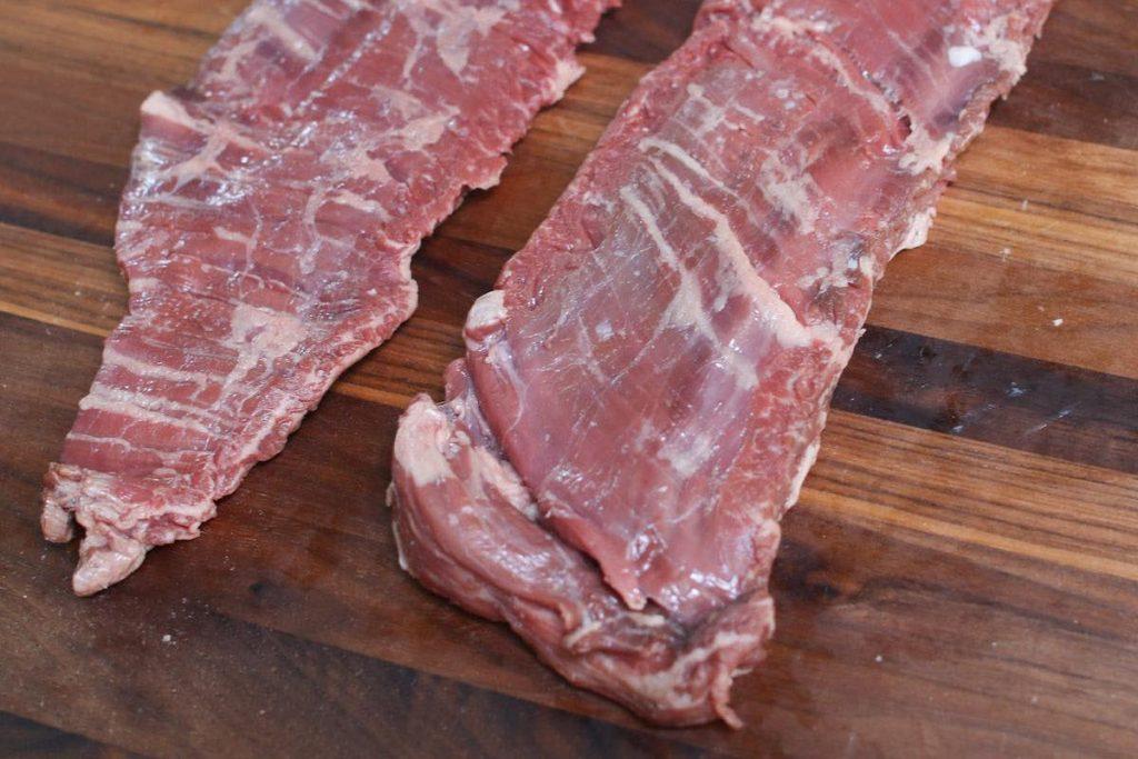 Raw skirt steak on a cutting board