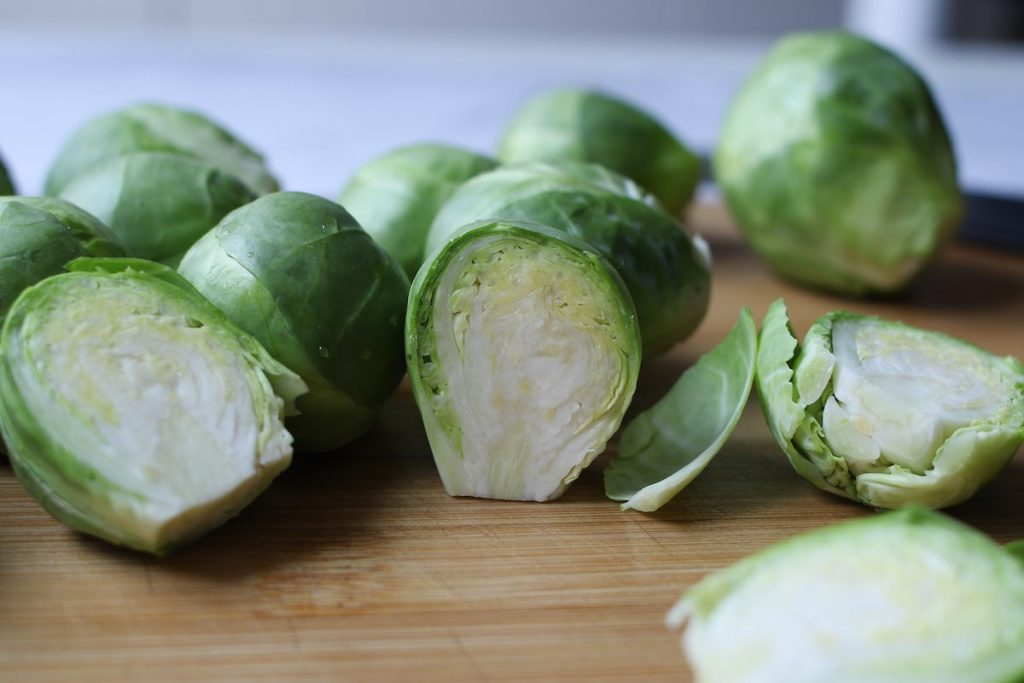 Halved Brussels sprouts on a wooden cutting board.