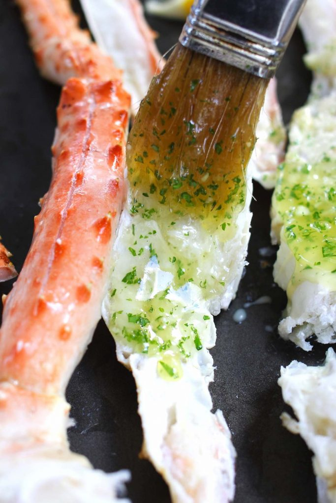 Brushing crab legs with the mixture of melted butter and chopped parsley.