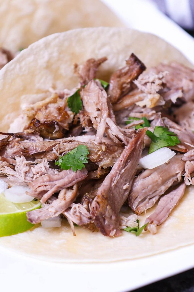 Shredded carnitas served on flour tortillas and topped with chopped onions and cilantro.