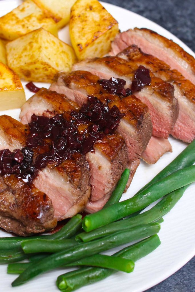 Sliced Sous Vide Duck Breast served with potatoes and green beans on a white plate.