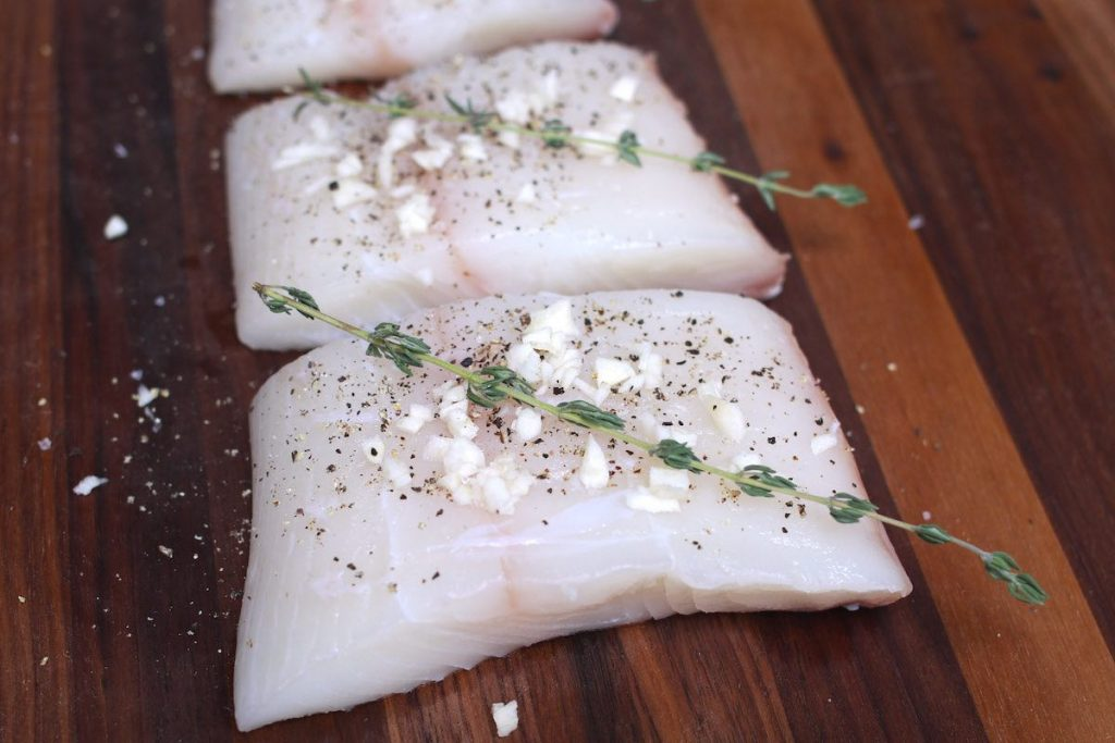 Fresh halibut filets seasoned with garlic, thyme, salt and pepper on a wooden cutting board.