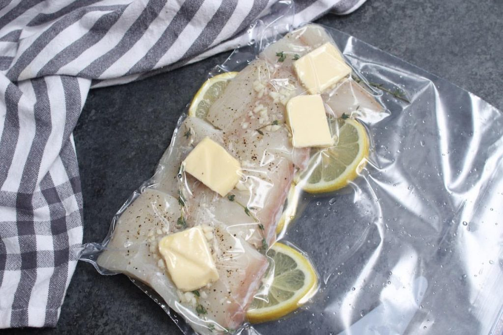 Seasoned halibut filet vacuum-sealed in a zip-lock bag.