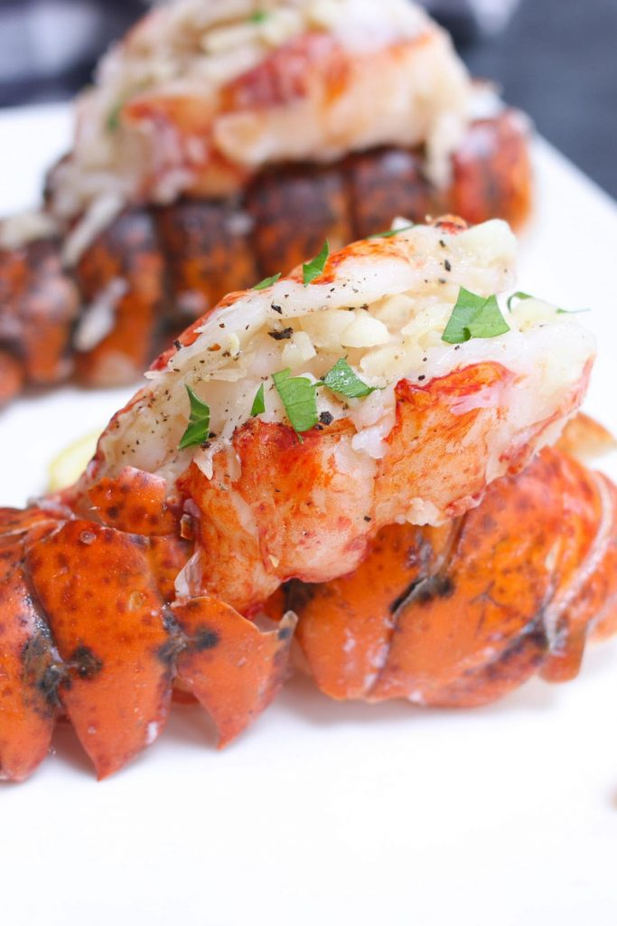 Sous Vide Lobster Tails sprinkled with chopped parsley and served on a white plate.