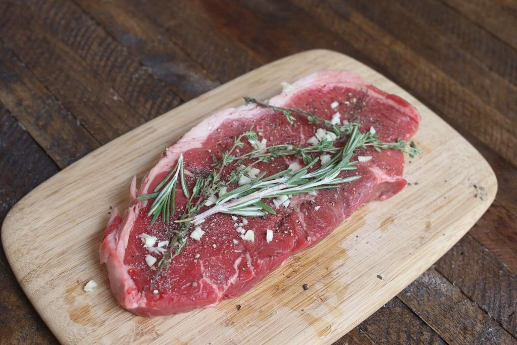 Seasoning sirloin steak.
