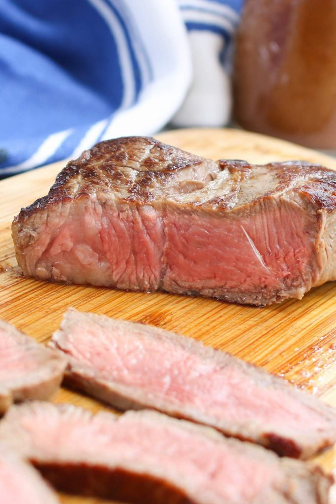 Cooked sirloin steak on a cutting board.