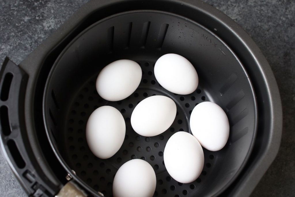 Placing eggs in the air fryer baskets.