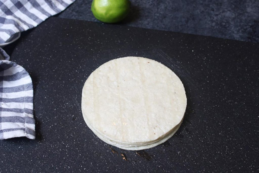 Placing 6 pieces of tortillas in a stack on a cutting board.