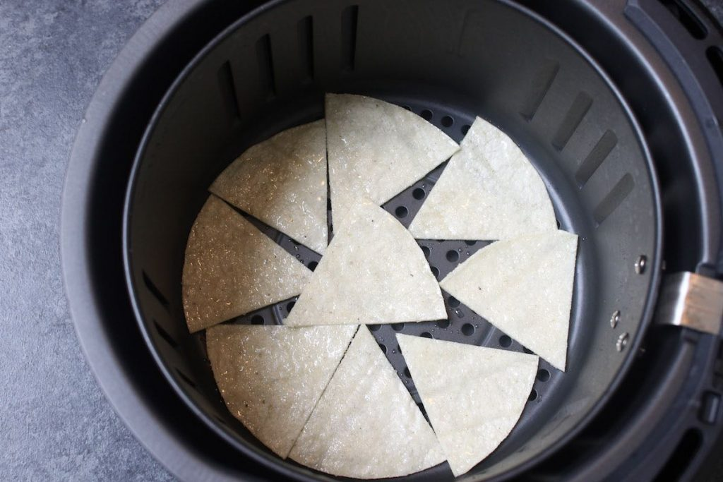 Spreading the tortilla pieces in the air-fryer basket in a single layer.