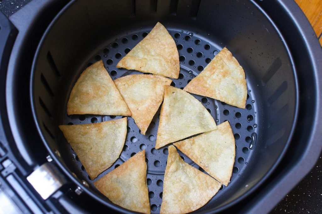 Freshly air fried tortilla chips in the basket.