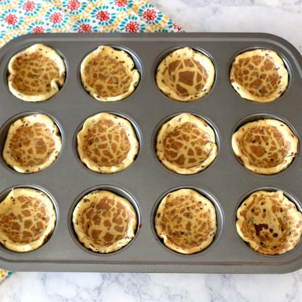 Flattened cinnamon roll in muffin tins.
