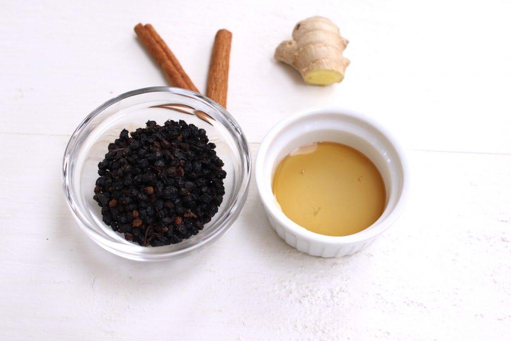 Elderberry tea key ingredients: dried elderberries, raw honey, cinnamon sticks, and fresh ginger.
