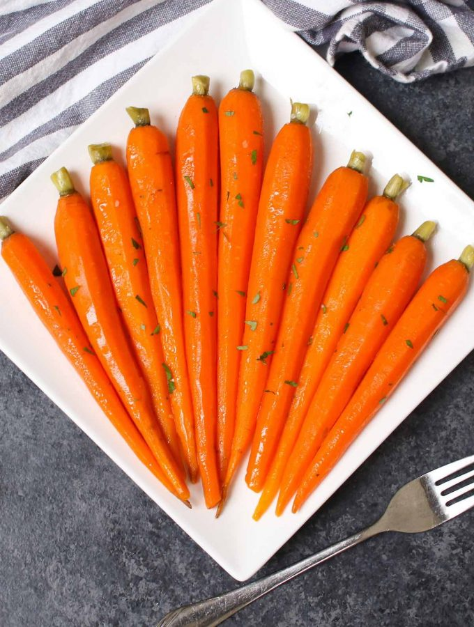 These Sous Vide Honey Glazed Carrots are tender and flavorful carrots simmered in a mixture of honey and butter, then topped with a sprinkling of parsley. The sous vide method transforms the carrots into the perfectly tender pieces. Sweet, savory and full of flavor, this recipe makes an amazing side dish for a holiday dinner or a week day meal. #SousVideCarrots