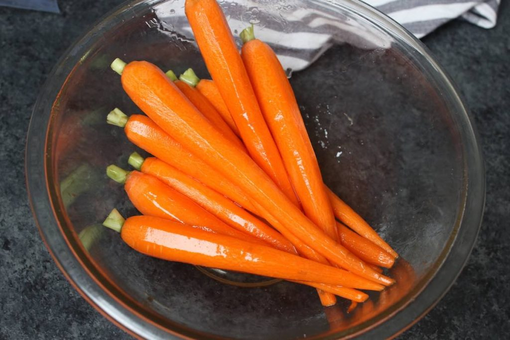 Peeled carrots seasoned with honey and salt in a clear mixing bowl.