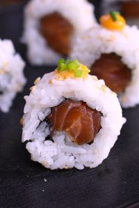 Spicy Salmon Rolls made with your favorite salmon tossed in sriracha spicy mayo, then rolled in nori seaweed sheet and fluffy sushi rice! You can easily customize the roll by adding other delicious ingredients. It's so much cheaper than the restaurant, and takes about 15 minutes from start to finish. I'll share with you the secrets to make the best spicy salmon sushi, with step by step photos! #SpicySalmonRoll