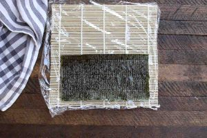 Laying out half of the nori sheet on top of bamboo mat.