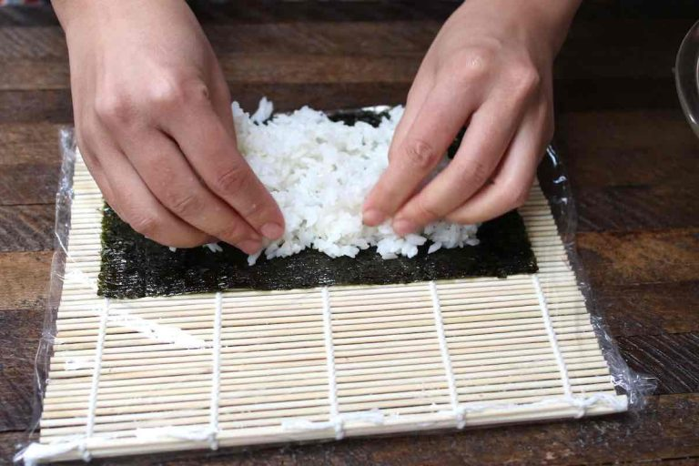 Spreading rice on top of the nori sheet.
