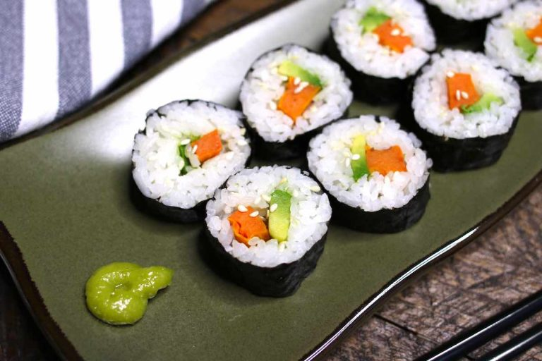 Sweet potato sushi rolls served with wasabi on a dark green plate.