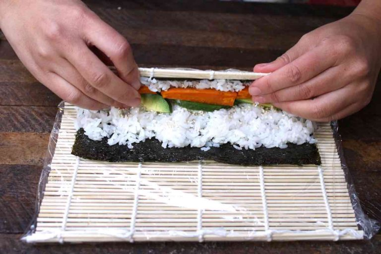 Place the thumbs underneath the bamboo mat and lift the edge up and over the filling.