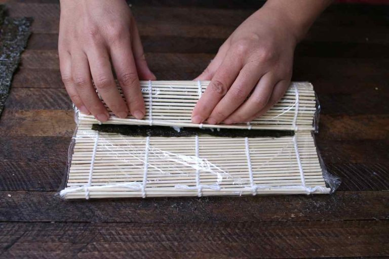 Peeling the mat back away as you continue to roll, so that the nori can be rolled into a cylinder.