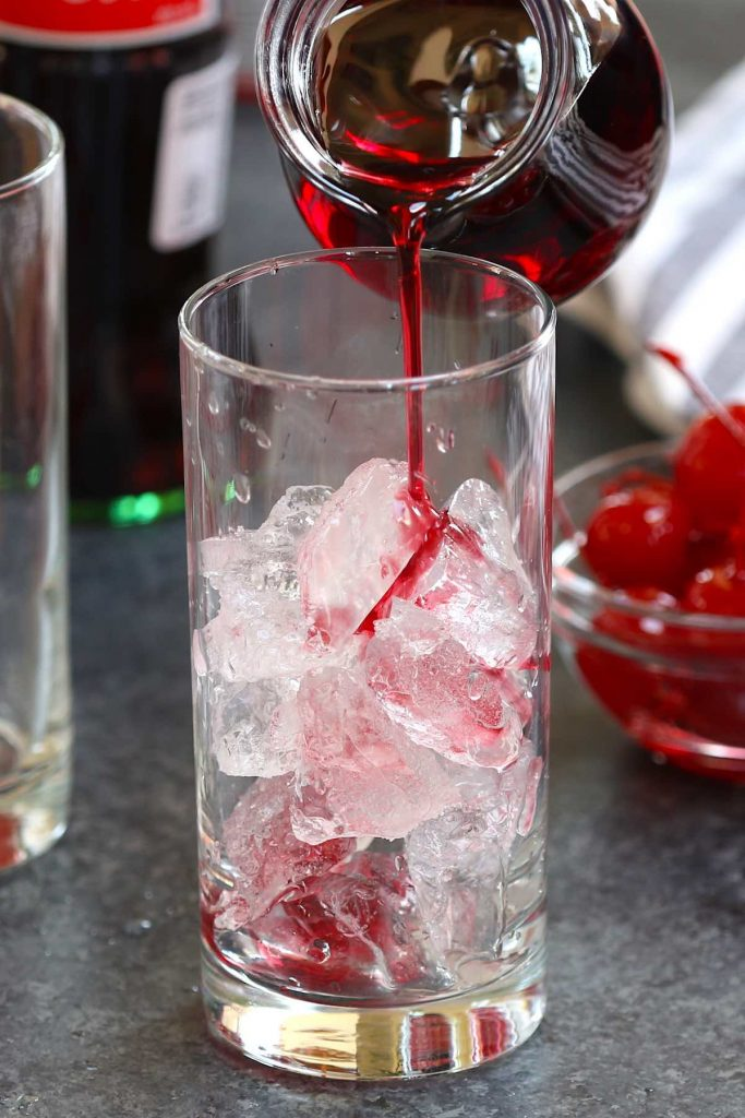 Pouring grenadine over ice cubs in a highball glass.