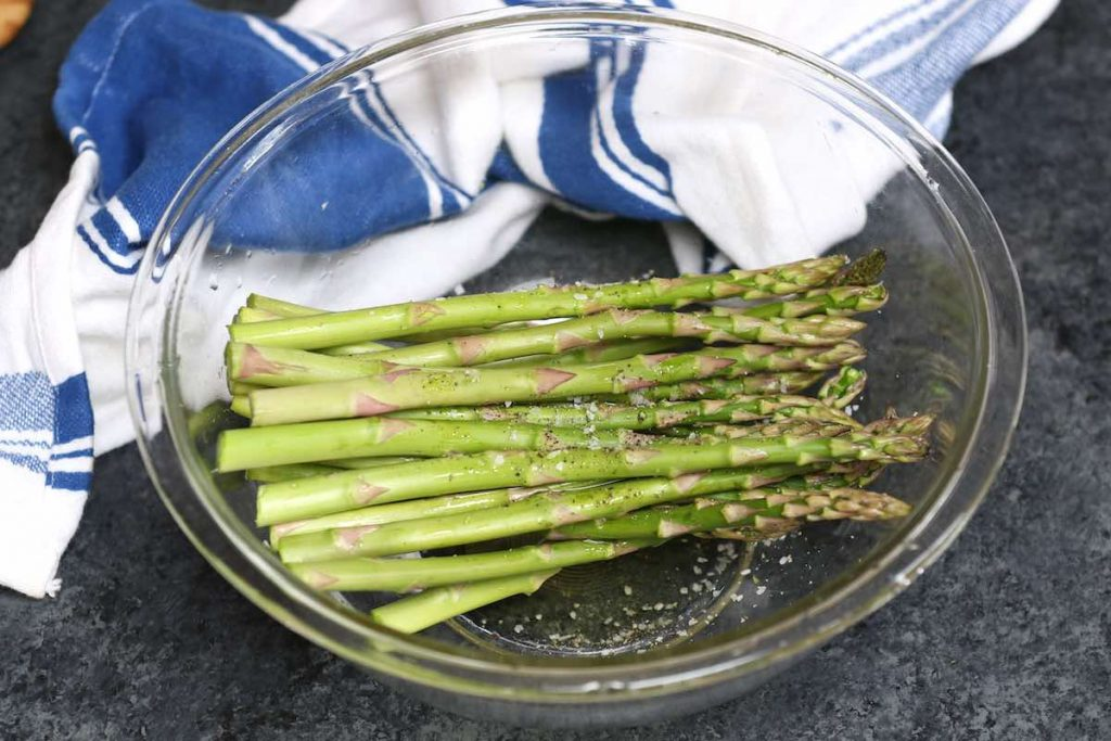 Adding asparagus, oil and seasoning in a clear mixing bowl.