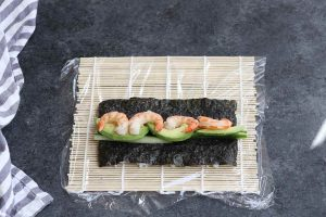 Adding poached shrimp, avocado, and cucumber on top of the nori sheet.
