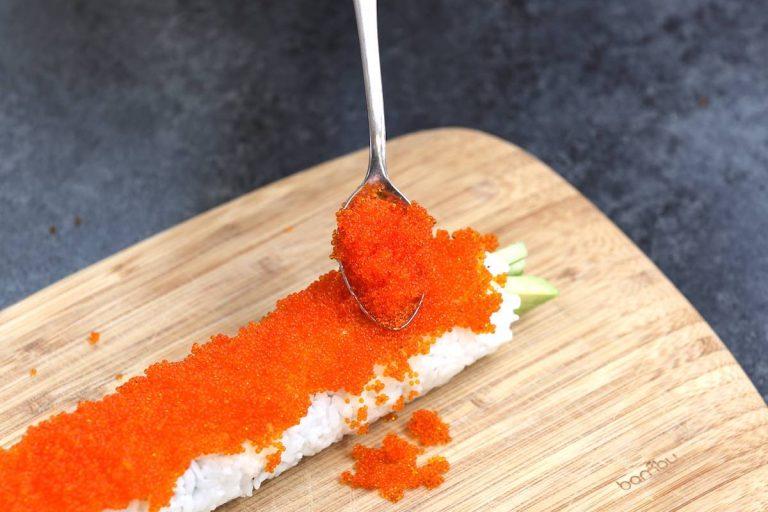 Adding tobiko onto the sushi roll.