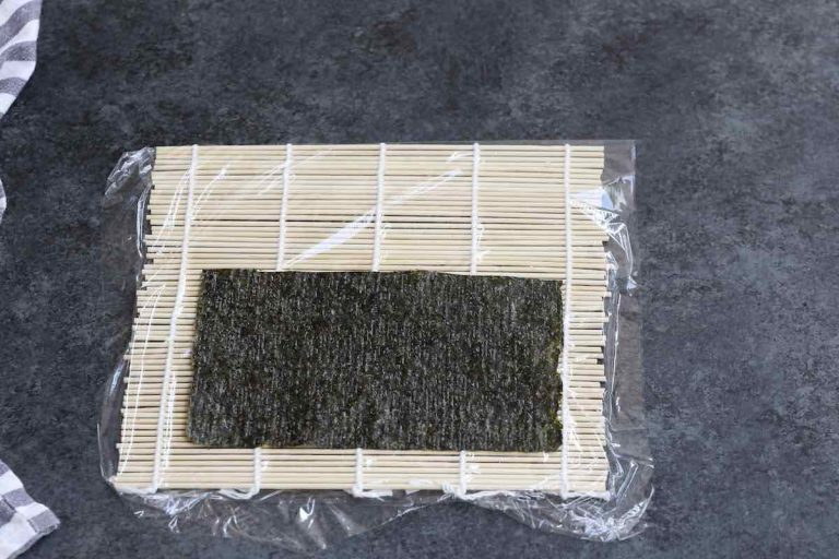 Placing half of the nori sheet on top of the bamboo mat.