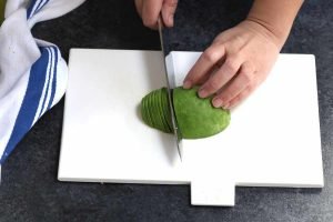 Cutting half of the avocado into thin slices.