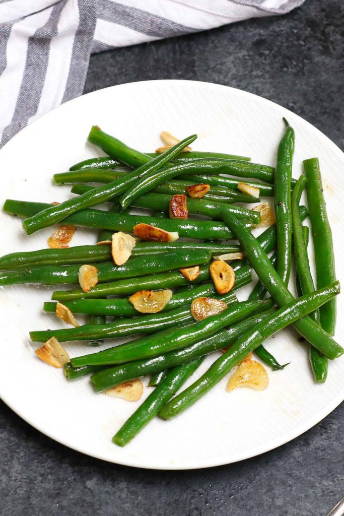 Sous vide green beans with garlic and oil served on a white plate.