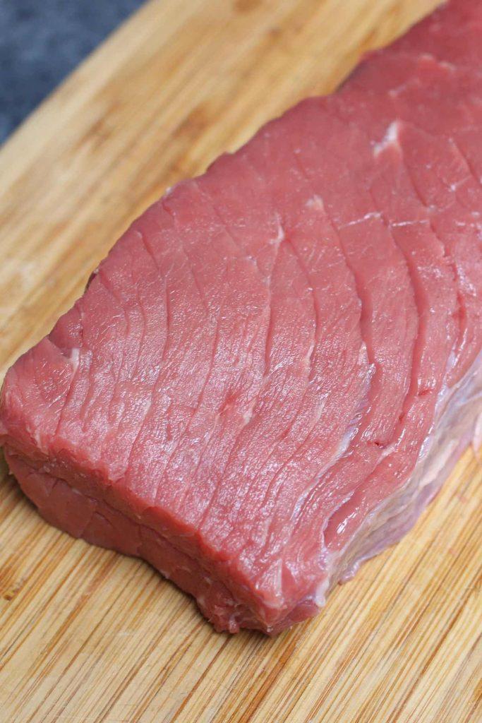 Raw top round steak on a cutting board.