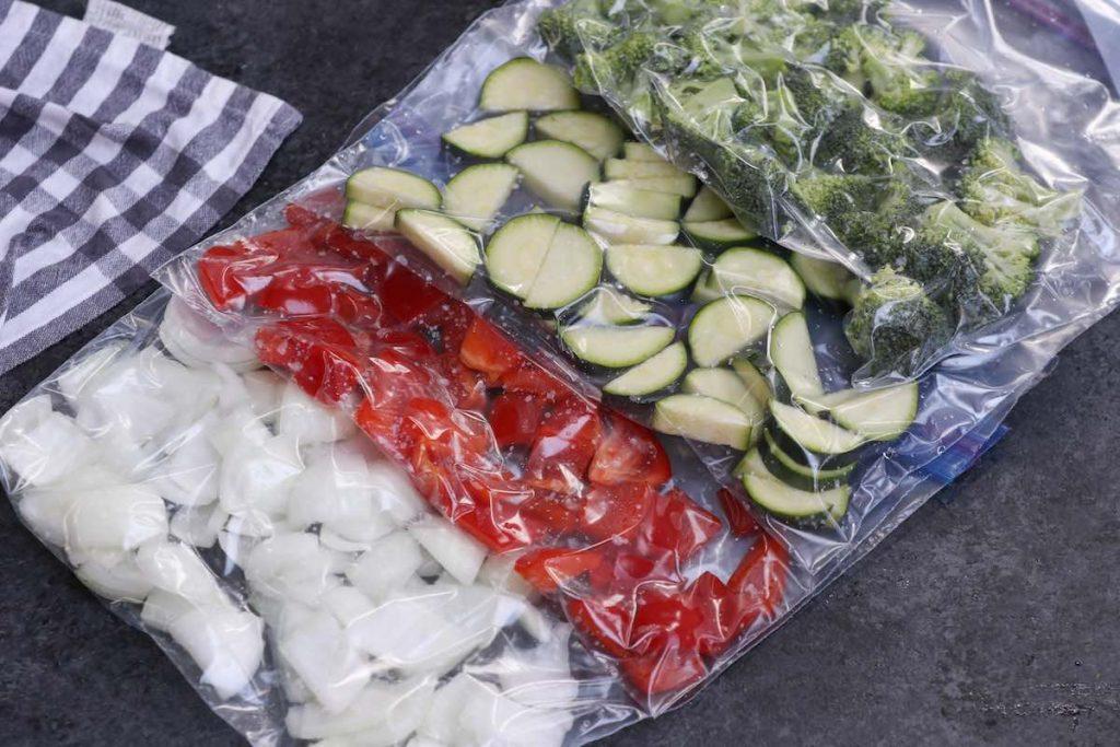 Vegetables vacuum-sealed in separate zip-top bags.