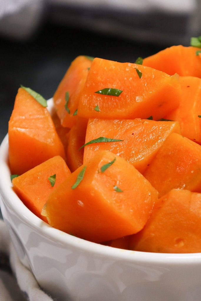 Sous vide sweet potatoes served in a white bowl, and topped with seasonings and chopped parsley.