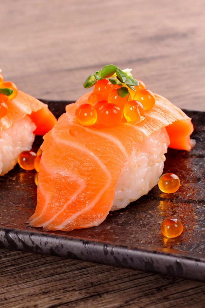 Using salmon caviar to garnish sashimi.
