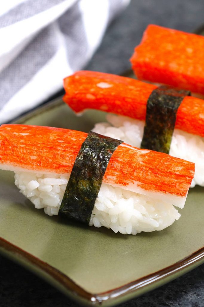Kanikama nigiri rolls on a Japanese plate.