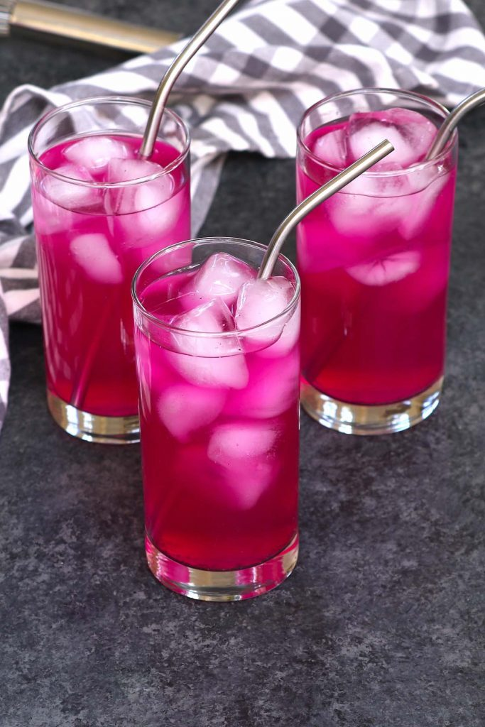 3 high-ball glasses of mango dragonfruit refresher on the counter, to be served.