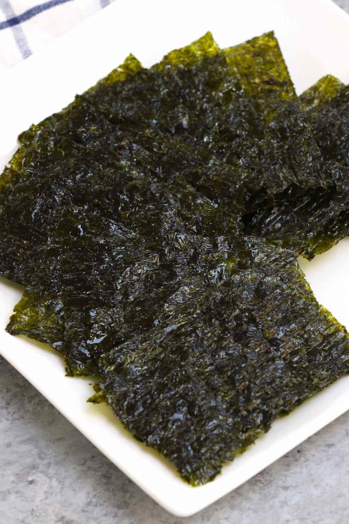 Small pieces of nori snacks on a white plate.