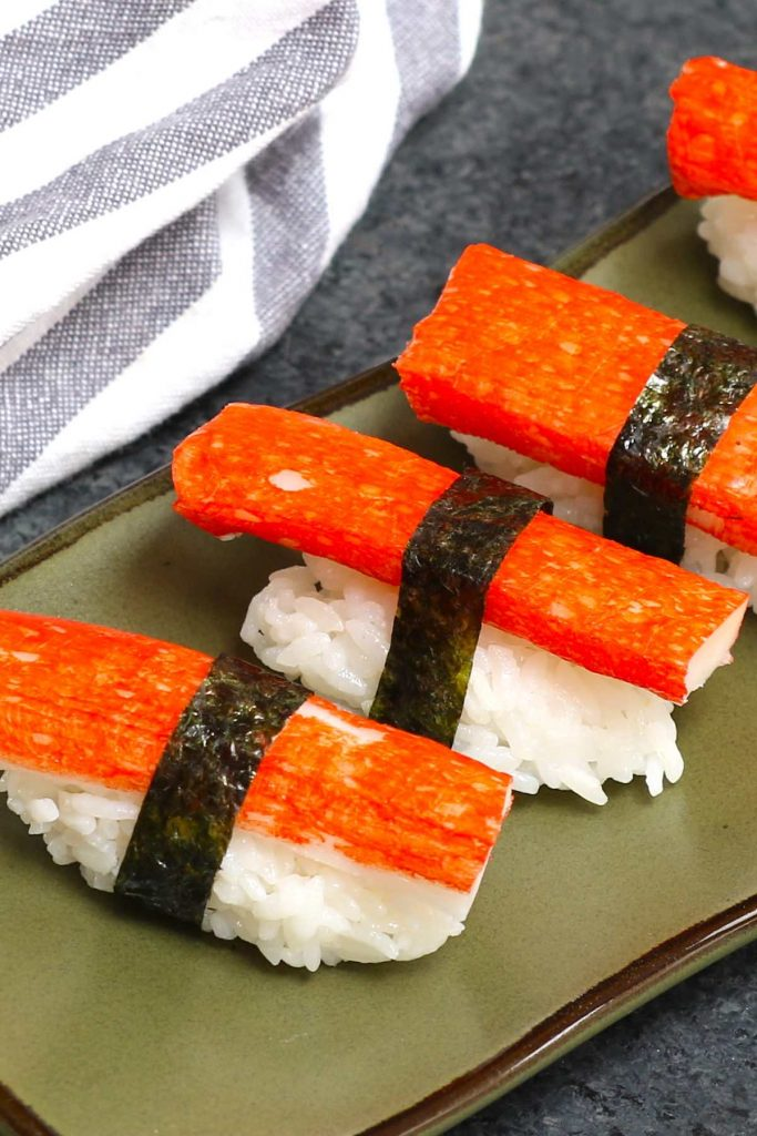 Nigiri sushi using nori strips to secure the imitation crab meat and rice.