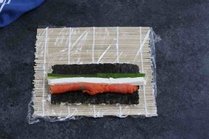 Place smoked salmon, cream cheese and cucumber strips on top of the nori.