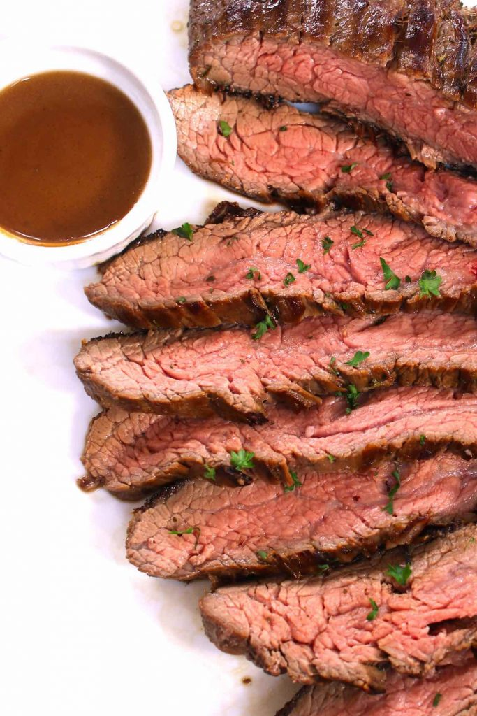 Sliced sous vide marinated flank steak served on a plate.