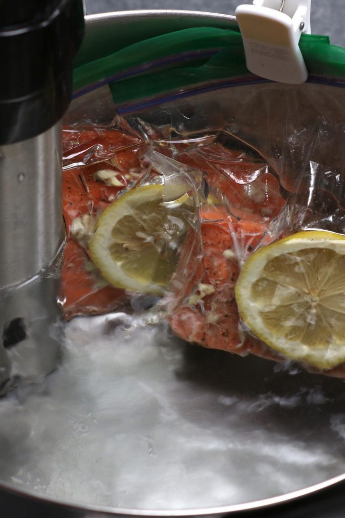 Sous vide cooking salmon in a water bath.