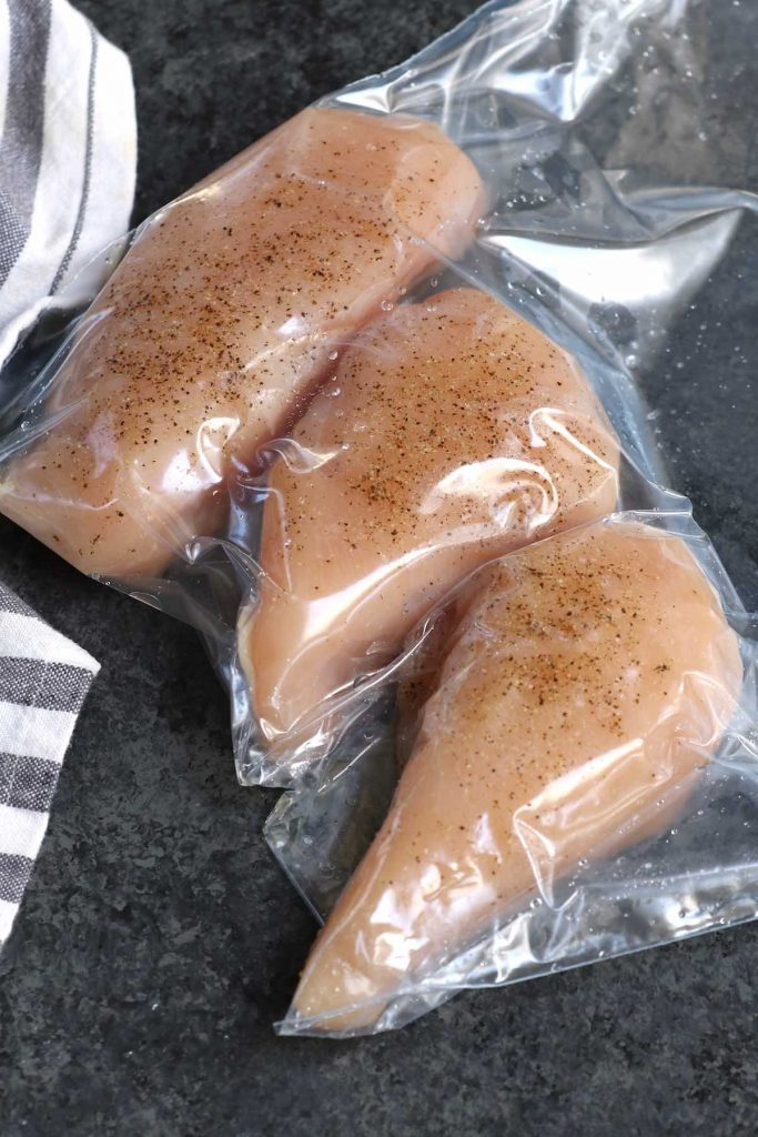 Seasoned chicken breasts vacuum-sealed in a zip-top bag.